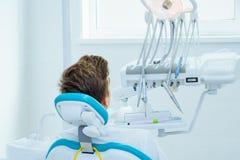 Prevenzione della carie dentale Adolescente alla sedia del ` s del dentista durante la procedura dentaria immagine stock libera da diritti