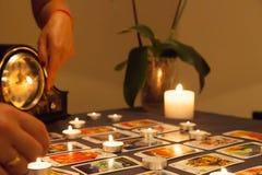 Previsão do futuro místico com velas e os cartões de jogo ateados fogo foto de stock