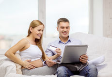 Previsione della famiglia con il computer portatile e la carta di credito Fotografia Stock