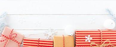 Prezentów pudełka i boże narodzenie ornamenty na białym drewnianym tle Obraz Royalty Free