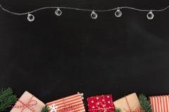 Prezentów pudełka i boże narodzenie ornamenty, rabatowy projekt na blackboard, Fotografia Stock