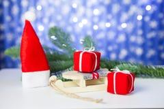 Prezentów pudełka na saniu i Santa kapeluszu na błękitnym tle, obrazy stock