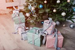 Prezentów pudełka pod nowego roku drzewem przy białym pokojem Szczęśliwa zima Holi Zdjęcia Royalty Free