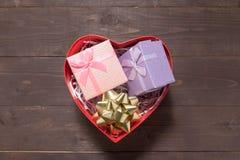 Prezentów pudełka są w serca pudełku na drewnianym tle z pustym, Obrazy Stock