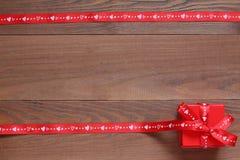 Prezent czerwieni faborki na drewnianej powierzchni i pudełko Zdjęcia Stock