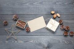 Prezent, karta, sosna rożki i cinnamonin na zmroku stole, Obrazy Royalty Free