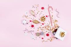 Prezent lub teraźniejszości pudełko z confetti gwiazdami, złotym faborkiem i wakacje dekoracją na pastelowych menchii tle, Bożena obraz stock