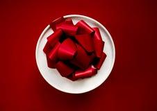 Prezent w białym round pudełku z czerwonym łękiem na czerwonym tle Odgórny widok Zdjęcia Royalty Free