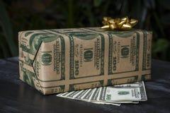 Prezent w pudełku z obrazkiem dolary i złoty łęk na da zdjęcie stock