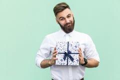 Prezent z miłością Ciekawy brodaty młody dorosły mężczyzna z prezenta pudełkiem na jasnozielonym tle Fotografia Stock