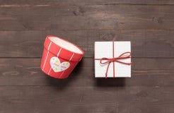Prezenta pudełko i kwiatu garnek jesteśmy na drewnianym tle z pustym Obrazy Royalty Free