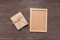 Prezenta pudełko i obrazek rama jesteśmy na drewnianym tle Fotografia Stock
