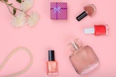 Prezenta pudełko, koraliki, butelka pachnidło, butelki z gwoździa połyskiem i kwiaty na różowym tle, zdjęcie royalty free