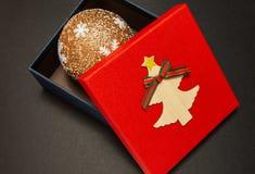 Prezenta pudełko w czerwieni z Bożenarodzeniową piłką, w górę obrazy royalty free