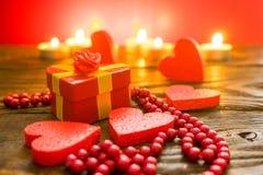 Prezenta pudełko w formie serca wiążącego z złocistym faborkiem i otaczającego dekoracyjnego serca tła płonącymi świeczkami zdjęcie royalty free