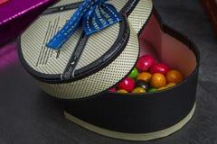 Prezenta pudełko w formie serca z cukierkami wśrodku obraz stock