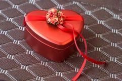 Prezenta pudełko w postaci serca w czerwieni na brązu tle zdjęcia stock