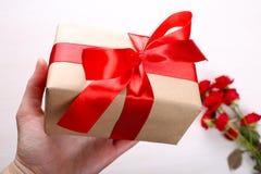 Prezenta pudełko w ręce i czerwonych różach Obrazy Royalty Free