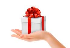 Prezenta pudełko w ręce z czerwonym łękiem i faborkami. Obrazy Royalty Free
