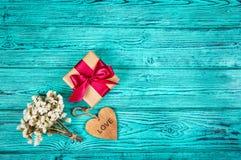 Prezenta pudełko z łękiem i drewniany serce na błękitnym drewnianym tle kosmos kopii Fotografia Stock