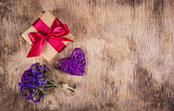 Prezenta pudełko z atłasowym faborkiem, łozinowym sercem i kwiatami na starym drewnianym tle, kosmos kopii Obrazy Royalty Free