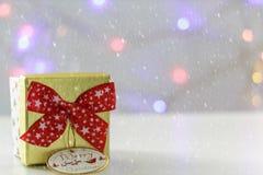 Prezenta pudełko z czerwonym łękiem i defocused bożonarodzeniowe światła na tle Z śnieżnym skutkiem fotografia stock