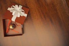 Prezenta pudełko z dźwięczenie dzwonem na drewnianej podłoga Zdjęcia Royalty Free