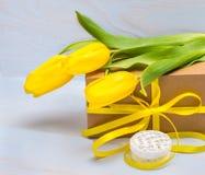 Prezenta pudełko z faborkiem i kolorów żółtych tulipanami obraz royalty free
