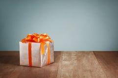 Prezenta pudełko z pomarańczowymi faborkami na drewnianym tle Obrazy Stock