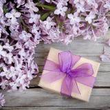Prezenta pudełko z purpurami ono kłania się i bez na drewnie Zdjęcia Royalty Free