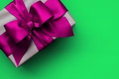 Prezenta pudełko z różowym faborkiem na zielonym tle zdjęcia stock