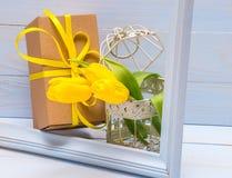 Prezenta pudełko z tasiemkowymi i żółtymi tulipanami w dekoracyjnej klatce zdjęcie royalty free