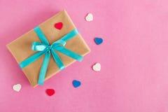 Prezenta pudełko zawijający rzemiosło papierowy i błękitny faborek z kolorowymi sercami na różowym tle Obraz Stock