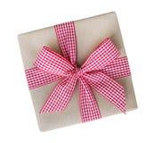 Prezenta pudełko zawijający w brąz przetwarzającym papierze z czerwonego i białego gingham tasiemkowego łęku odgórnym widokiem od zdjęcia stock
