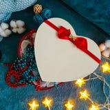 Prezenta pudełko w formie serca z czerwonym łękiem przeciw tłu wygodne turkusowe koc obramiać w dekoracyjnej bawełnie, obraz royalty free