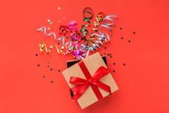 Prezenta pudełko z colourful streamers na czerwonym tle fotografia stock