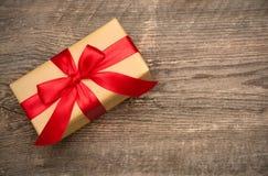 Prezenta pudełko z czerwonym faborkiem na drewnianym tle Fotografia Royalty Free
