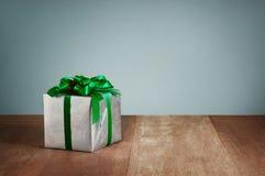 Prezenta pudełko z zielonymi faborkami na drewnianym tle Obraz Royalty Free