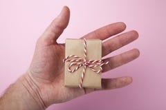 Prezenta zbliżenie Piękny prezent w mężczyzna ręce Różowy tło zdjęcia royalty free