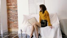 Prezentacja nowa kolekcja odziewa, zadziwiająca kobieta na szpilkach siedzi w modnej odzieży na białej kanapie przy fotografią zdjęcie wideo