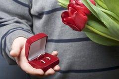 Prezenty dla nasi bliskich Mężczyzna trzymają bukiet czerwoni tulipany w jej ręce W innej ręce, otwarty aksamita pudełko czerwony Fotografia Royalty Free