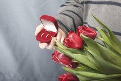 Prezenty dla nasi bliskich Mężczyzna trzymają bukiet czerwoni tulipany w jej ręce W innej ręce, otwarty aksamita pudełko czerwony Zdjęcie Stock