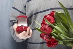 Prezenty dla nasi bliskich Mężczyzna trzymają bukiet czerwoni tulipany w jej ręce W innej ręce, otwarty aksamita pudełko czerwony Obrazy Royalty Free