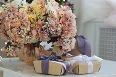 Prezenty i waza z bujny menchiami kwitną z iluminować girlandami zdjęcia royalty free