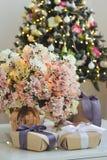 Prezenty i waza z bujny menchiami kwitną z iluminować girlandami obrazy royalty free