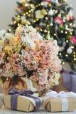 Prezenty i waza z bujny menchiami kwitną z iluminować girlandami fotografia royalty free