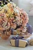Prezenty i waza z bujny menchiami kwitną z iluminować girlandami obraz stock
