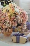 Prezenty i waza z bujny menchiami kwitną z iluminować girlandami fotografia stock