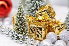 Prezenty w złocie pakuje blisko choinek Zdjęcia Royalty Free