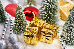 Prezenty w złocie pakuje blisko choinek Fotografia Stock